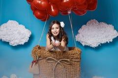 O voo bonito pequeno da menina no coração vermelho balloons o dia de Valentim Imagens de Stock Royalty Free