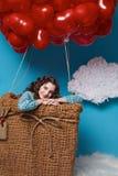 O voo bonito pequeno da menina no coração vermelho balloons o dia de Valentim Imagem de Stock Royalty Free