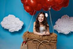 O voo bonito pequeno da menina no coração vermelho balloons o dia de Valentim Fotos de Stock