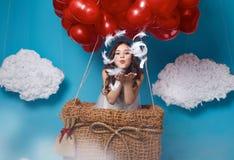 O voo bonito pequeno da menina no coração vermelho balloons o dia de Valentim Foto de Stock Royalty Free