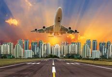 O voo do avião decola da pista de decolagem no por do sol Fotos de Stock