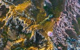 O voo do balão sobre rochas e campos antigos em Cappadocia é kn Imagem de Stock