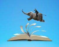 O voo do elefante da equitação do homem na parte superior que lança páginas do livro aberto é Fotos de Stock