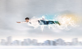 O voo do superman do herói acima da cidade com fumo saiu atrás Fotografia de Stock