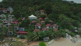 O voo do zangão das casas de praia da ilha do mar de Tailândia, a árvore selvagem da natureza das montanhas e o hotel da palma re video estoque