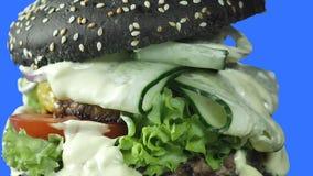 O voo invertido da câmera é close-up através de um hamburguer suculento com um bolo preto, verdes, um molho branco poluído e o a filme
