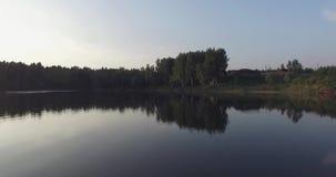 O voo sobre o lago, espaço livre da câmera gosta de um espelho Reflete as árvores na costa, na grama verde, na casa de madeira e  video estoque