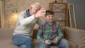 O vovô aprecia a vitória de seu neto no jogo do console O ancião está sentando-se no sofá com um menino gordo novo video estoque