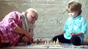 O vov? e o neto consider?veis est?o jogando a xadrez ao passar o tempo junto em casa Rapaz pequeno que joga a xadrez com seu video estoque