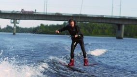 O Wakeboarder que salta à superfície da àgua alto Desportista profissional que faz o truque filme