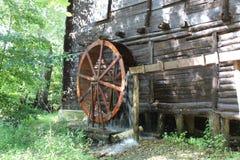 O watermill de trabalho roda com água de queda na vila imagens de stock