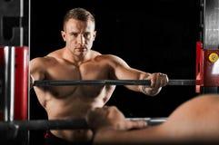 O weightlifter mantém suas mãos no barbell e olha-o fotografia de stock