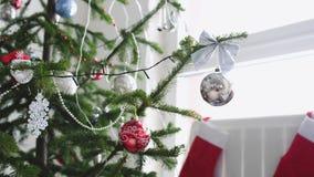 O White Christmas à moda interior com a árvore de abeto decorada e pendura peúgas pela janela Movimento lento 3840x2160 vídeos de arquivo