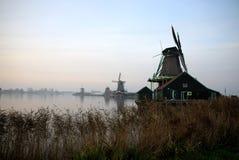 O windemill na cidade de Kinderdijk na Holanda, com a paisagem da vila, do rio, do prado e da exploração agrícola fotografia de stock