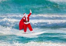 O windsurfer de Santa Claus com presentes despede surfar em ondas de oceano Imagem de Stock