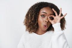 O wow olha de divertimento Retrato de modelo fêmea de pele escura emotivo bonito interessado e intrigado na camiseta foto de stock