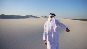 O xeique árabe dos UAE do emirado masculino novo ativo exulta na vida e anda com as extensões do deserto na noite clara filme