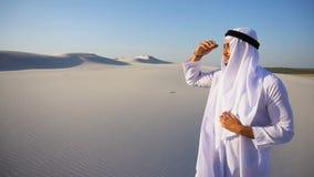 O xeique bonito do emirado olha para fora na caravana da distância dos camelos, estando entre o deserto largo no dia quente video estoque