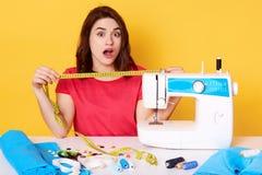 O yuong bonito costura o trabalho na máquina de costura, não tem bastante pano, sentando-se com boca aberta, surpreendeu a expres foto de stock