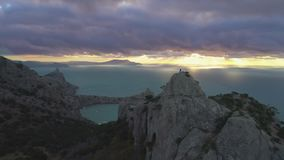 O zangão é voo inverso rápido sobre o homem do montanhista que está sobre a rocha no nascer do sol Silhueta do homem de negócio C video estoque