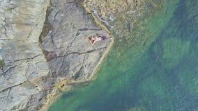 O zangão aproxima a menina que encontra-se na rocha entre o oceano de turquesa vídeos de arquivo