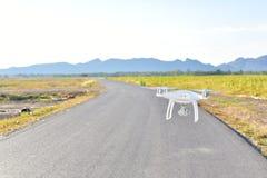 O zangão branco decola da terra e o voo para toma a foto aérea Foto de Stock