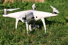 O zangão branco do quadcopter com a câmara digital 4K na grama está pronto para que decola voe no ar para tomar fotos, grava a me Fotos de Stock