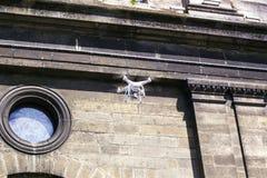 O zangão branco do quadrocopter voa contra a catedral do católico da parede imagem de stock