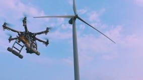 O zangão decola das mãos de uma menina perto de uma turbina eólica, movimento lento filme