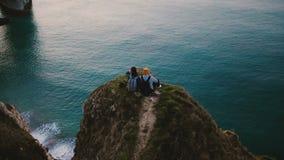 O zangão inclina para baixo sobre a vista para o mar de observação do por do sol dos pares românticos felizes que senta-se sobre  video estoque