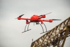 O zangão industrial vermelho voa sobre o faci industrial das estruturas do metal Fotografia de Stock