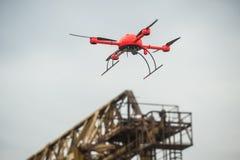 O zangão industrial vermelho voa sobre o faci industrial das estruturas do metal Imagens de Stock Royalty Free
