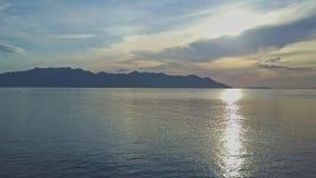 O zangão mostra o nascer do sol fantástico acima do oceano contra montes filme