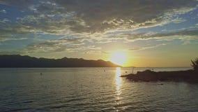 O zangão move-se ao longo da silhueta da costa contra o nascer do sol fantástico filme