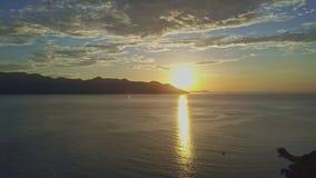 O zangão move-se ao longo do trajeto fantástico de Sun no oceano no nascer do sol vídeos de arquivo