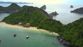 O zangão move-se lentamente sobre a ilha verde bonita com hotel video estoque