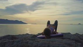 O zangão move-se para em torno da menina que faz exercícios da ioga na pedra filme