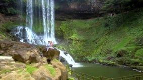 O zangão move-se para a menina do indivíduo na rocha pelo rio contra a cachoeira filme