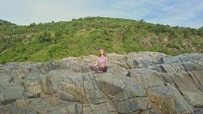 O zangão move-se para a menina que senta-se na pose da ioga na rocha alta vídeos de arquivo