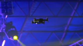 O zangão ou Quadrocopter em um festival de música que voa sobre a cena e disparam na multidão na câmera filme