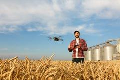 O zangão paira na frente do fazendeiro com o controlador remoto nas mãos perto do elevador de grão Quadcopter voa perto do piloto Imagem de Stock Royalty Free
