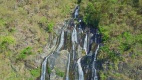 O zangão pendura acima da cachoeira alta entre rochas nas montanhas filme