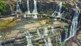 O zangão pendura perto das cachoeiras que fluem dos penhascos video estoque