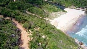 O zangão pendura sobre a estrada marrom no monte acima da praia da lagoa filme