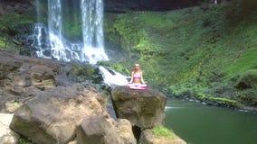O zangão remove da menina que senta-se na pose dos lótus na pedra pelo rio e pela cachoeira video estoque