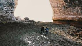O zangão segue a caminhada feliz dos pares do turista ao longo da praia incrível do mar da maré baixa do alabastro sob o arco gig filme