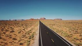 O zangão segue o carro que move-se ao longo da estrada americana icónica da estrada do deserto no vale dos monumentos com a skyli filme