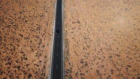 O zangão segue a condução de carro de prata ao longo da estrada americana seca da paisagem do deserto, o conceito do aquecimento  filme