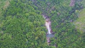 O zangão voa altamente acima dos montes verdes com cachoeiras do rio video estoque
