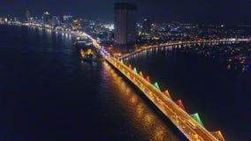 O zangão voa ao longo da ponte da baía na cidade da noite no beira-mar filme
